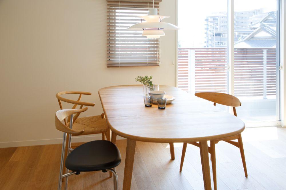 無垢材で作られたダイニングテーブルと北欧デザインのチェアと照明