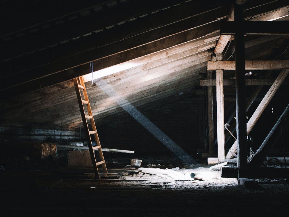 梯子が立てかけられた窓から光の差し込む屋根裏部屋