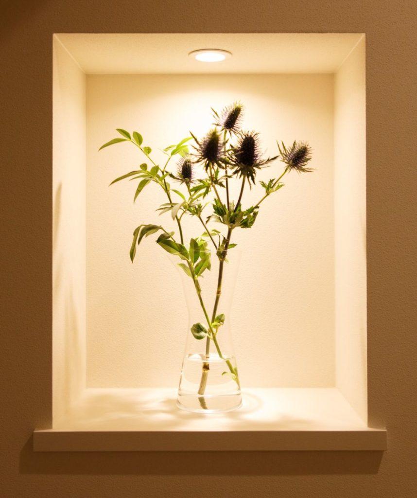 ダウンライトで照らされた花器と草花