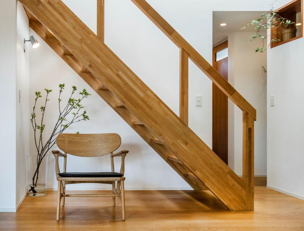 階段下のギャラリースペースに置かれた北欧デザインのラウンジチェアと植物