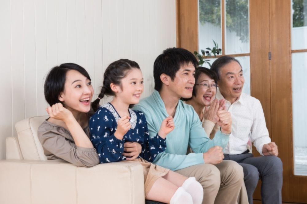 二世帯家族がソファでテレビを見ている様子
