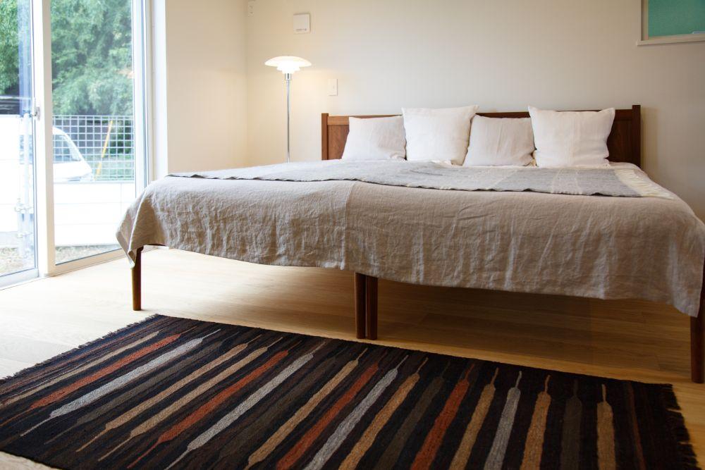 ラグの敷かれたシンプルな寝室
