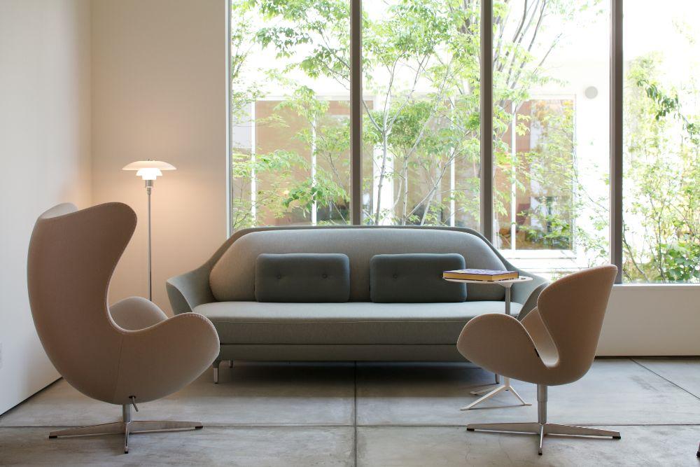 シンプルでミニマムなデザインのソファやラウンジチェアが置かれた土間空間