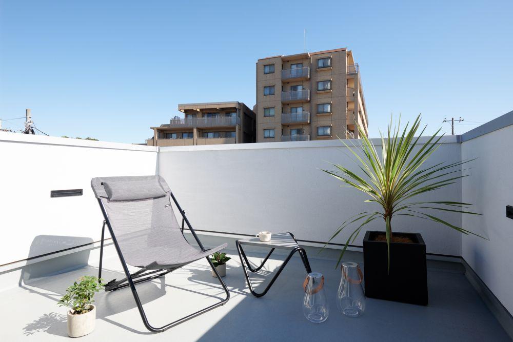 小スペースの屋上に置かれたアウトドア家具とグリーン