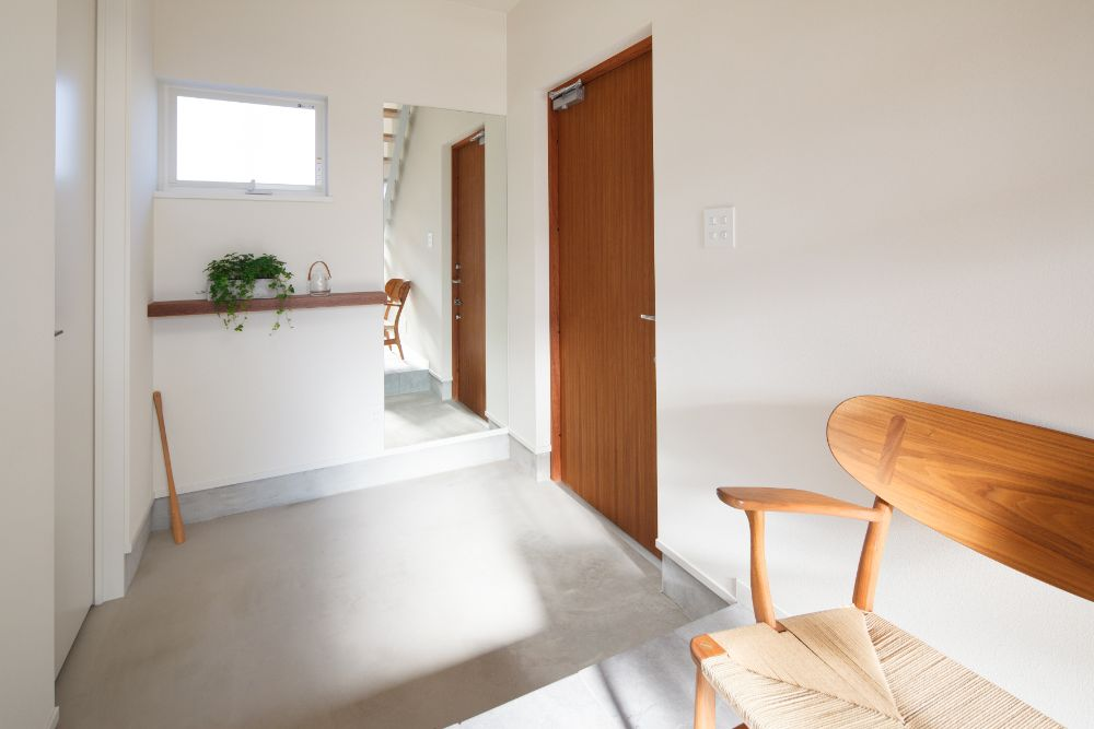 白い壁に玄関ドアの木部が映える玄関