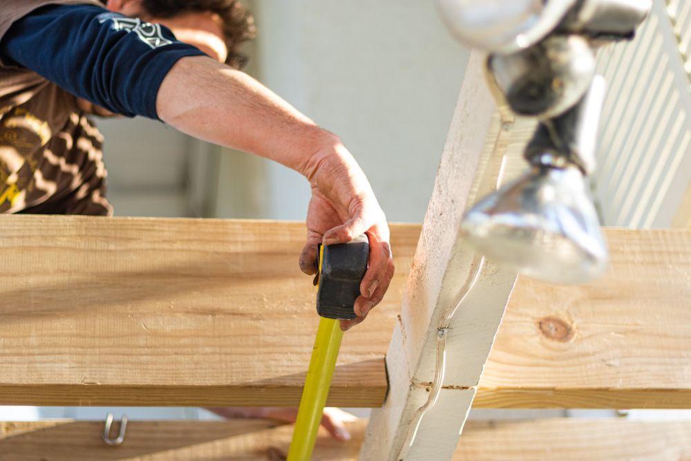 大工さんがメジャーで木材を図っている様子