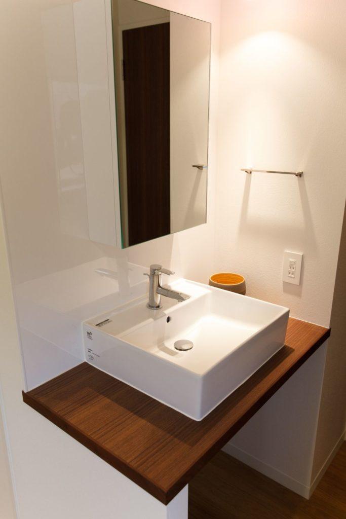 ウォルナット材の天板に白い洗面器が映える落ち着いた雰囲気の洗面スペース