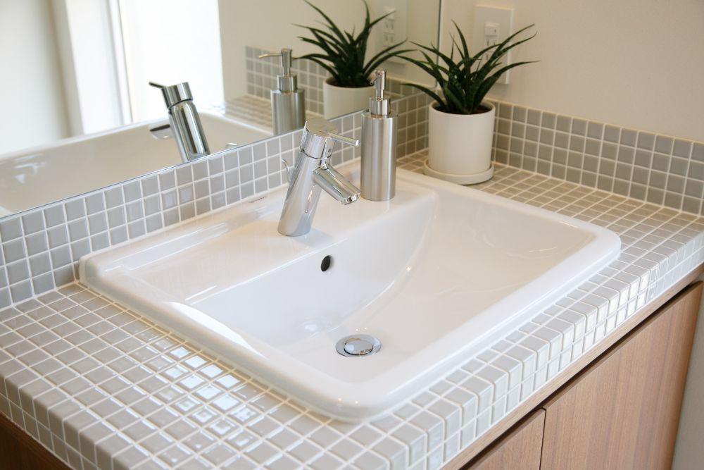 ライトグレーのタイルと白い洗面器で造られたシンプルな洗面