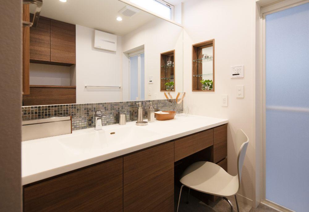 つなぎ目のない1枚鏡が印象的な化粧スペースと併用された洗面スペース