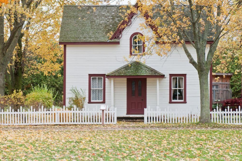 白い外壁に赤い縁取りのかわいい外観の家
