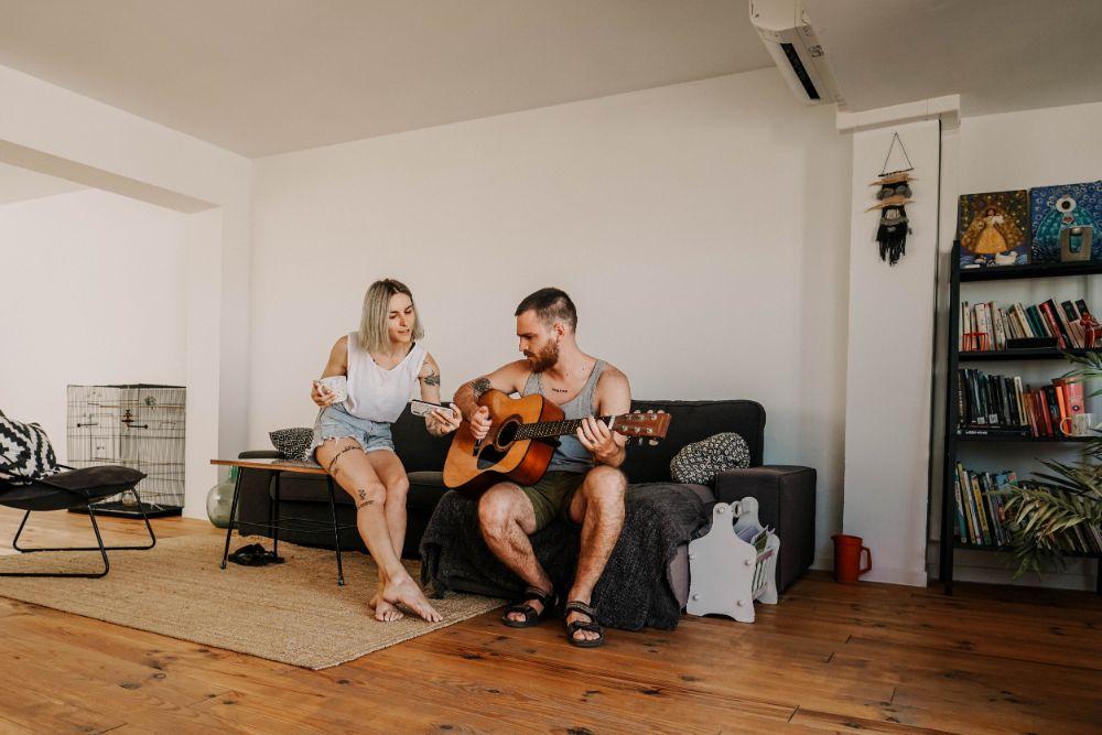 ギターを持つ男性とコーヒーと携帯を持つ女性が話している様子