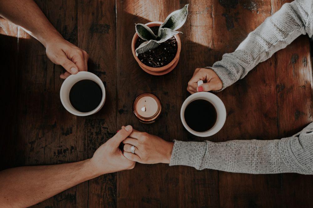 コーヒーを飲みながら手を握る恋人