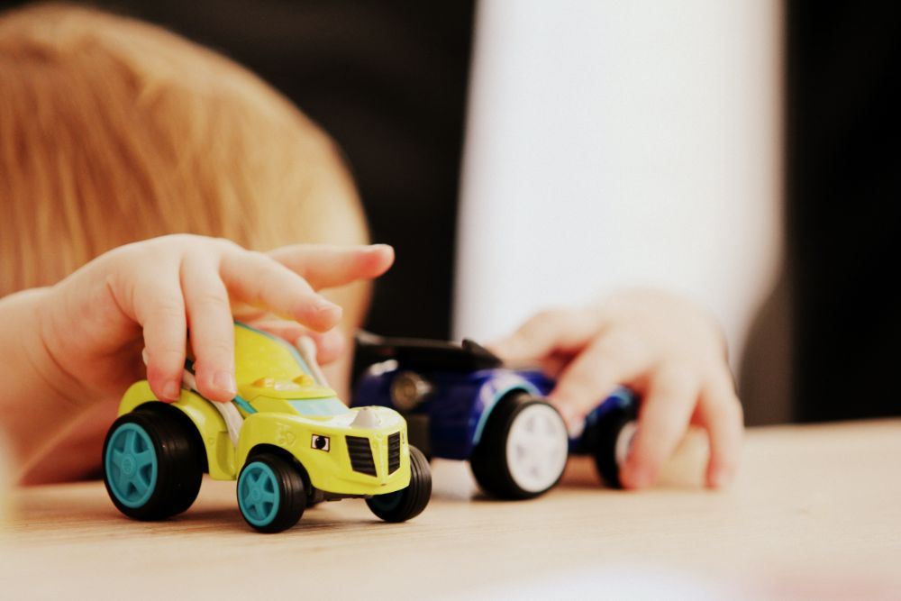 子供が車のおもちゃで遊んでいる様子