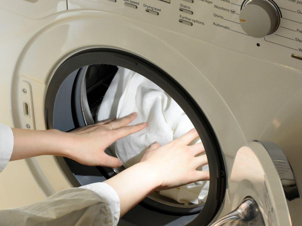 洗濯機に洗濯物を入れている様子