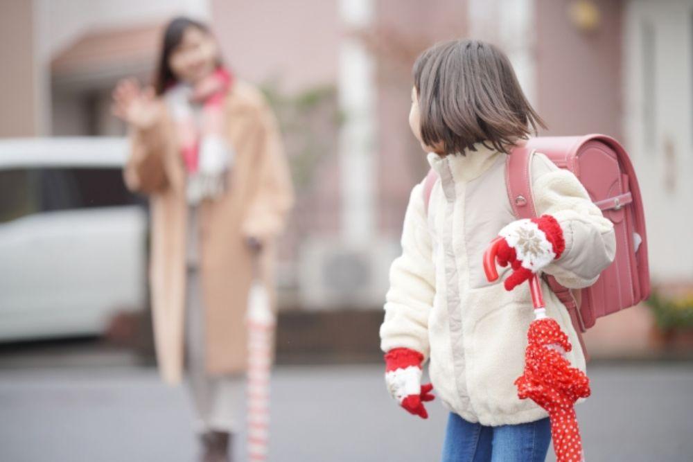 小学生が登校する様子を見送る女性