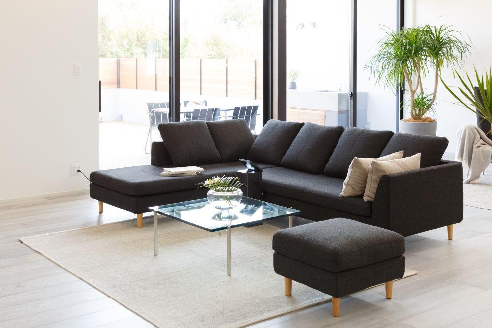 明るい空間を引き締めるように置かれたシックな色合いのソファ