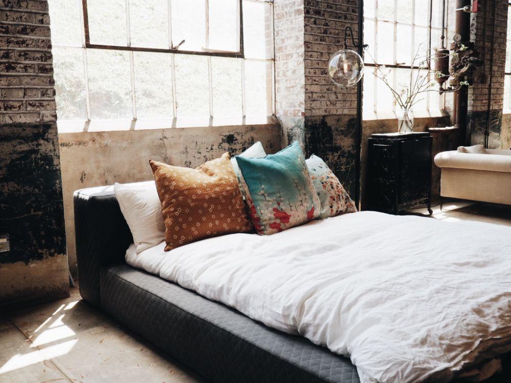 無機質な壁の部屋に置かれたベッド