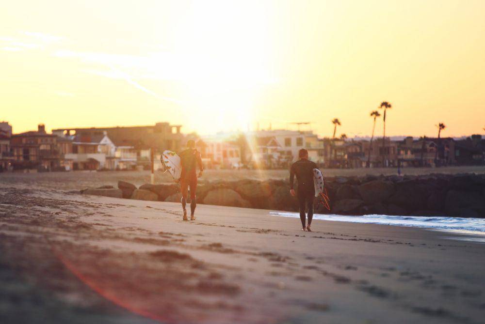 サーファーが砂浜を歩いている様子