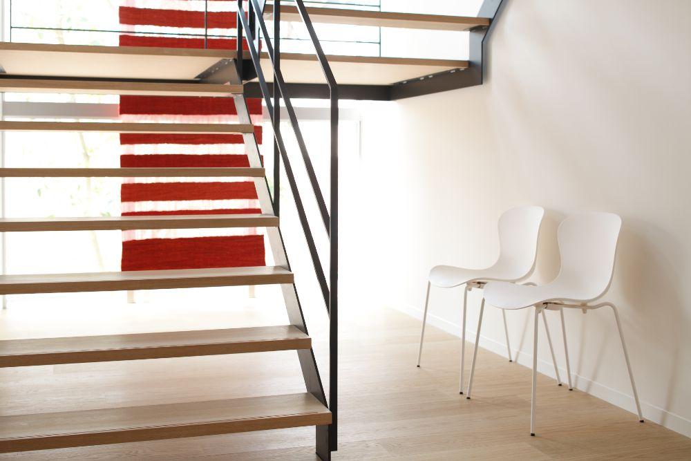スケルトン階段の下に置かれた椅子2脚