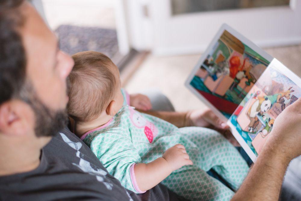 赤ちゃんに絵本を読んでいる男性