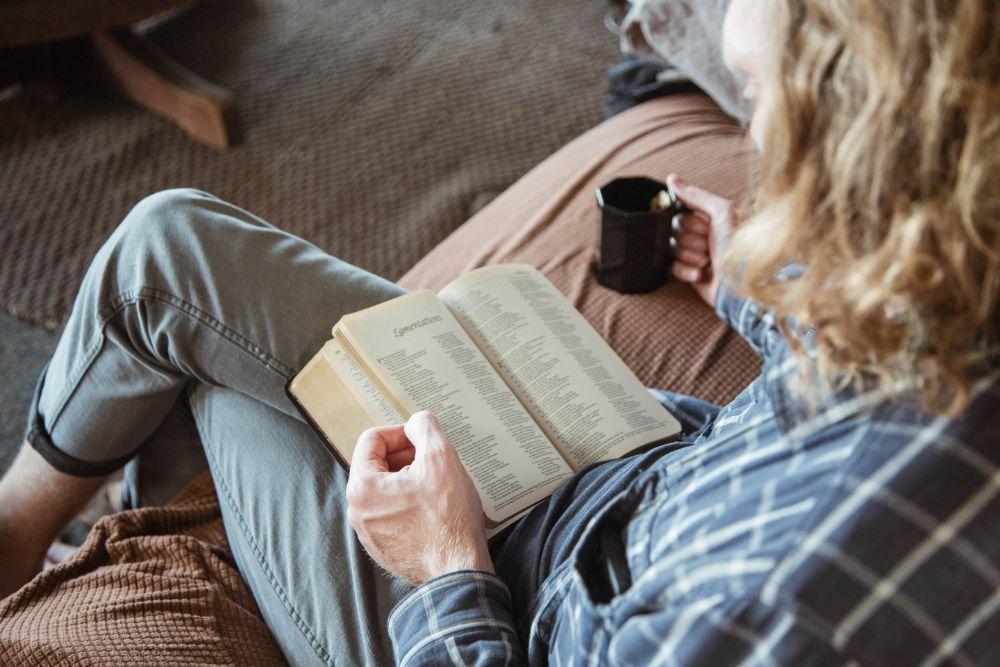 コーヒーを飲みながら本を読んでいる人