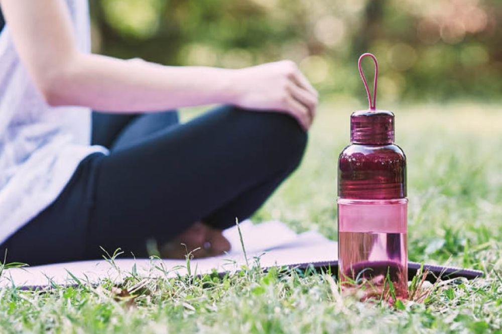 枚ボトルを持ち歩いて外でヨガをしている