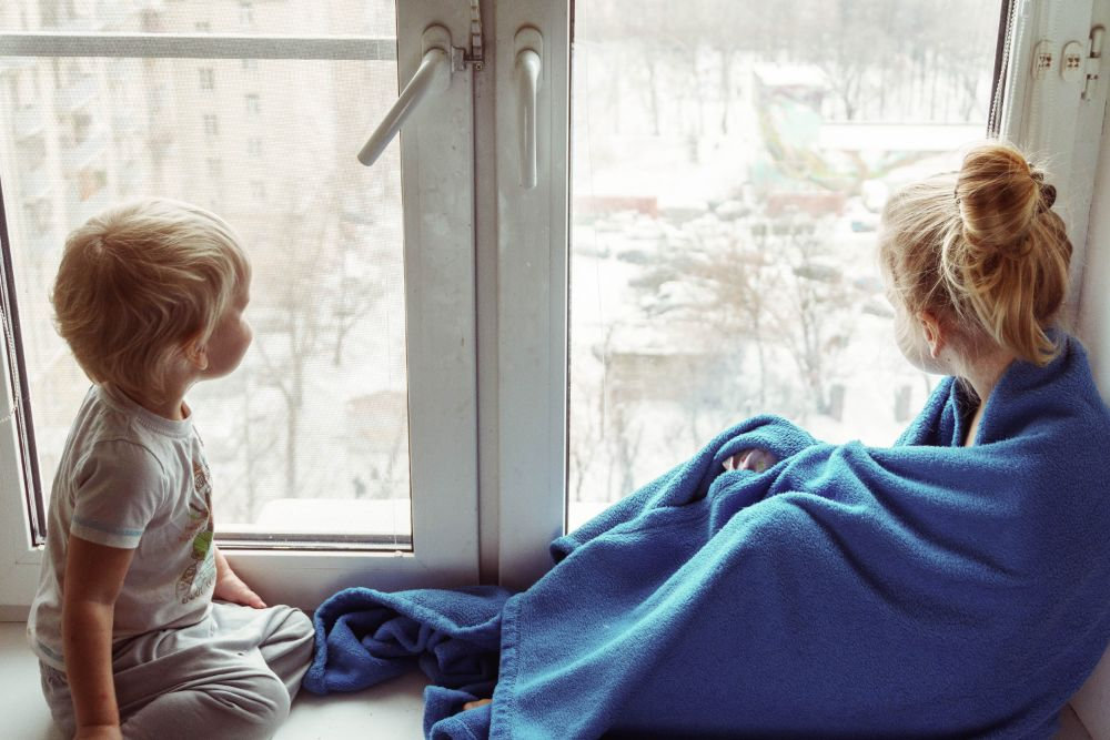 窓辺で姉弟が外を眺めている様子